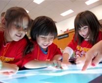 three children use a smart table