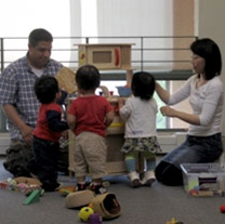 two adults and three early learners play together